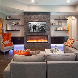 Diseño de sala de estar cerrada, clásica renovada, grande, con paredes grises, suelo de baldosas de porcelana, chimenea lineal, marco de chimenea de piedra y televisor colgado en la pared