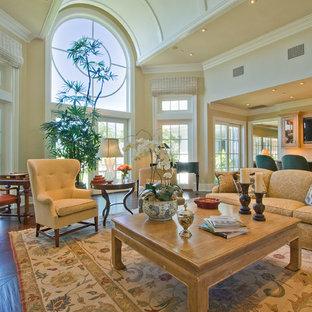 Exemple d'une salle de séjour victorienne ouverte avec un mur beige, un sol en bois foncé et un téléviseur fixé au mur.