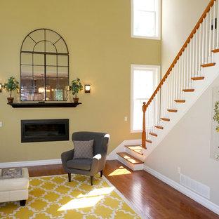 Cette photo montre une grand salle de séjour tendance fermée avec un mur jaune, un sol en bois foncé, cheminée suspendue, un manteau de cheminée en métal, aucun téléviseur et un sol marron.