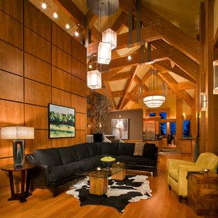 他の地域の大きいラスティックスタイルのおしゃれなファミリールーム (無垢フローリング、ベージュの壁、暖炉なし、埋込式メディアウォール、茶色い床) の写真