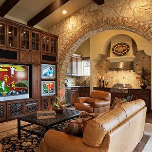 Esempio di un grande soggiorno mediterraneo aperto con pareti beige, parete attrezzata, angolo bar, pavimento in gres porcellanato, nessun camino e pavimento beige