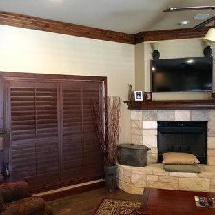 オースティンの中サイズのトロピカルスタイルのおしゃれな独立型ファミリールーム (ベージュの壁、濃色無垢フローリング、コーナー設置型暖炉、石材の暖炉まわり、壁掛け型テレビ、茶色い床) の写真