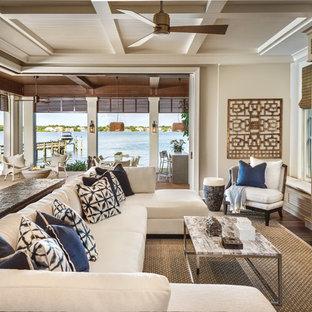 Diseño de sala de estar abierta, actual, grande, sin chimenea, con paredes beige, suelo de madera oscura y televisor retractable