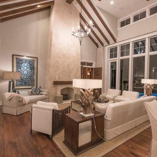 Aménagement d'une grande salle de séjour exotique ouverte avec un mur beige, un sol en bois clair, une cheminée standard, un manteau de cheminée en pierre et aucun téléviseur.