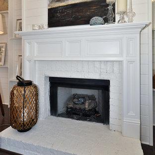 バーミングハムのトラディショナルスタイルのおしゃれなファミリールーム (ベージュの壁、濃色無垢フローリング、標準型暖炉、レンガの暖炉まわり、茶色い床) の写真