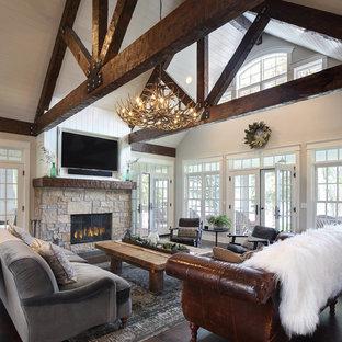 Modelo de sala de estar abierta, de estilo de casa de campo, de tamaño medio, con paredes blancas, suelo de madera oscura, chimenea de doble cara, marco de chimenea de piedra, televisor retractable y suelo marrón