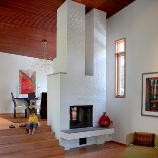 ボストンのコンテンポラリースタイルのおしゃれなファミリールーム (白い壁、両方向型暖炉、レンガの暖炉まわり) の写真