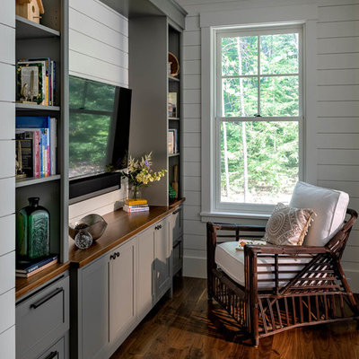 Small arts and crafts enclosed dark wood floor and brown floor family room library photo in Boston with white walls and a media wall