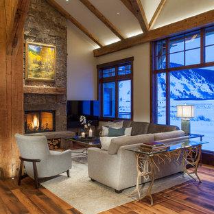 Cette photo montre une salle de séjour montagne ouverte avec un mur blanc, un sol en bois brun, une cheminée standard, un manteau de cheminée en pierre, un téléviseur indépendant et un sol marron.