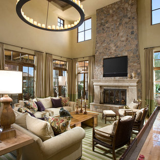 Large mediterranean open plan family and games room in Phoenix with beige walls, a stone fireplace surround, a game room, carpet, a standard fireplace, a built-in media unit and green floors.