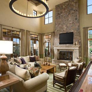 Großer, Offener Mediterraner Hobbyraum mit beiger Wandfarbe, Kaminumrandung aus Stein, Teppichboden, Kamin, Multimediawand und grünem Boden in Phoenix