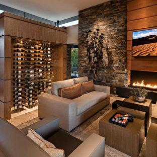 フェニックスの大きいサンタフェスタイルのおしゃれなオープンリビング (マルチカラーの壁、磁器タイルの床、標準型暖炉、石材の暖炉まわり、壁掛け型テレビ、ベージュの床) の写真