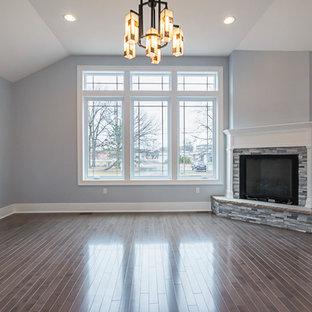 Esempio di un soggiorno stile americano di medie dimensioni e aperto con pareti grigie, pavimento in laminato, camino ad angolo, cornice del camino in pietra e pavimento marrone