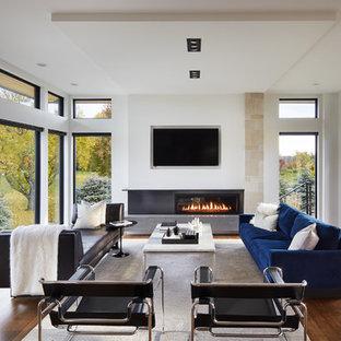 Imagen de sala de estar abierta, minimalista, con paredes blancas, chimenea lineal, televisor colgado en la pared y suelo de madera oscura