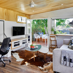 Design ideas for a small contemporary open concept family room in Sydney with white walls, medium hardwood floors and a wall-mounted tv.