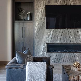 ラスベガスの中サイズのコンテンポラリースタイルのおしゃれな独立型ファミリールーム (ベージュの壁、磁器タイルの床、横長型暖炉、金属の暖炉まわり、壁掛け型テレビ) の写真