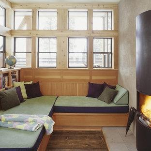 Foto de sala de estar con biblioteca cerrada, rústica, pequeña, sin televisor, con paredes beige, chimenea tradicional, marco de chimenea de metal y suelo beige