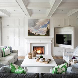 ミネアポリスのビーチスタイルのおしゃれなファミリールーム (白い壁、淡色無垢フローリング、標準型暖炉、埋込式メディアウォール、ベージュの床) の写真
