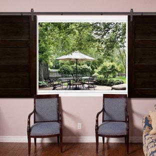 Modelo de sala de estar cerrada, campestre, de tamaño medio, sin chimenea, con paredes rosas, suelo de madera en tonos medios y suelo marrón
