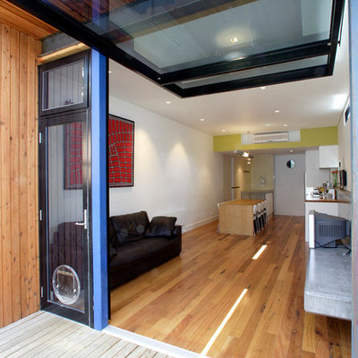 Example of a trendy open concept medium tone wood floor family room design in Melbourne with white walls