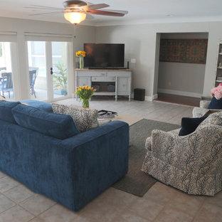 タンパの広いビーチスタイルのおしゃれな独立型ファミリールーム (グレーの壁、セラミックタイルの床、暖炉なし、コーナー型テレビ、ベージュの床) の写真