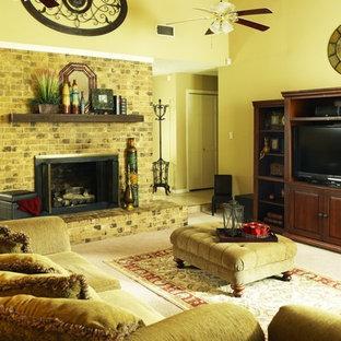 Immagine di un soggiorno tradizionale con pareti gialle, moquette, camino classico, cornice del camino in mattoni e TV autoportante