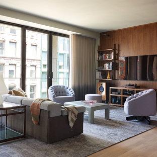 Foto de sala de estar con biblioteca abierta, actual, sin chimenea, con paredes marrones, suelo de madera clara y televisor colgado en la pared