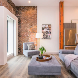 タンパの中サイズのインダストリアルスタイルのおしゃれなファミリールーム (白い壁、据え置き型テレビ、無垢フローリング、暖炉なし、茶色い床) の写真