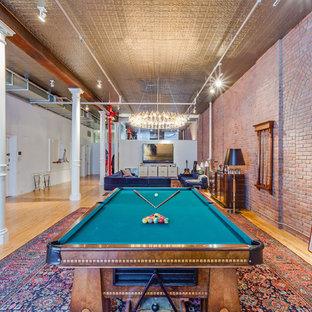 Idee per un ampio soggiorno industriale aperto con sala giochi, parquet chiaro e TV a parete
