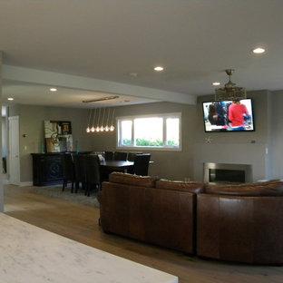 サンディエゴの大きいビーチスタイルのおしゃれなファミリールーム (グレーの壁、淡色無垢フローリング、標準型暖炉、金属の暖炉まわり、壁掛け型テレビ) の写真