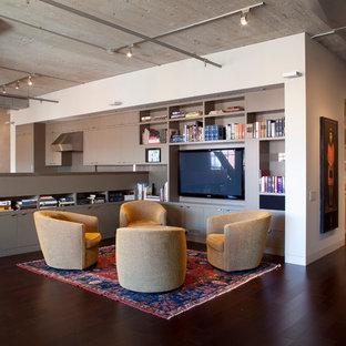Ispirazione per un piccolo soggiorno industriale aperto con pareti beige, parquet scuro e parete attrezzata