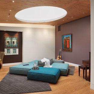 Esempio di un soggiorno design aperto con sala della musica, pareti viola, pavimento in legno massello medio e nessun camino