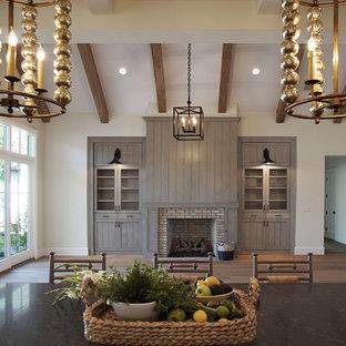 Esempio di un grande soggiorno classico con pareti bianche, pavimento in legno massello medio, camino classico, cornice del camino in mattoni, pavimento marrone e soffitto a volta