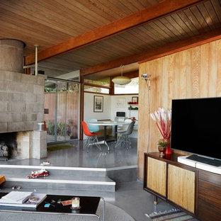 シアトルの中くらいのインダストリアルスタイルのおしゃれなオープンリビング (ゲームルーム、ベージュの壁、コンクリートの床、コーナー設置型暖炉、コンクリートの暖炉まわり、据え置き型テレビ、グレーの床) の写真