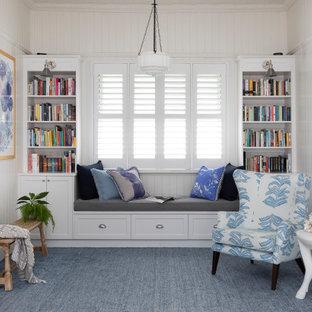 Cette photo montre une salle de séjour avec une bibliothèque ou un coin lecture chic de taille moyenne et ouverte avec un mur blanc, aucun téléviseur, moquette, aucune cheminée, un sol bleu et du lambris.