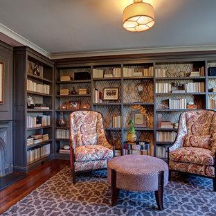 Idee per un soggiorno tradizionale di medie dimensioni e chiuso con libreria, pareti viola, pavimento in legno massello medio, camino classico e cornice del camino in metallo