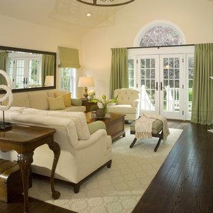 Foto di un soggiorno classico di medie dimensioni con pareti beige, pavimento in compensato, camino classico, cornice del camino in cemento e pavimento marrone