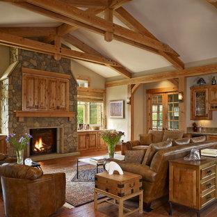 Großes Klassisches Wohnzimmer mit beiger Wandfarbe, braunem Holzboden, Kamin, Kaminsims aus Stein, verstecktem TV und Hausbar in Denver
