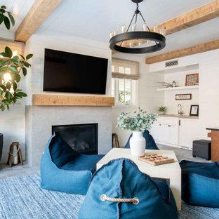 ロサンゼルスの巨大なビーチスタイルのおしゃれなオープンリビング (石材の暖炉まわり、白い壁、標準型暖炉、グレーの床、表し梁、塗装板張りの天井、塗装板張りの壁) の写真