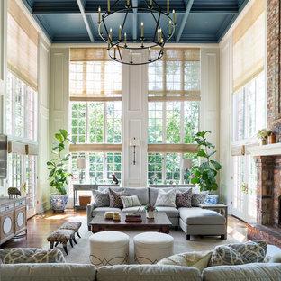 Пример оригинального дизайна: огромная открытая гостиная комната в классическом стиле с бежевыми стенами, паркетным полом среднего тона, стандартным камином, фасадом камина из кирпича, телевизором на стене и коричневым полом