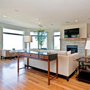 グランドラピッズの大きいビーチスタイルのおしゃれなファミリールーム (ミュージックルーム、ベージュの壁、淡色無垢フローリング、標準型暖炉、石材の暖炉まわり、壁掛け型テレビ) の写真