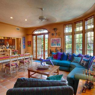 Foto di un grande soggiorno tropicale aperto con pareti arancioni e pavimento in terracotta