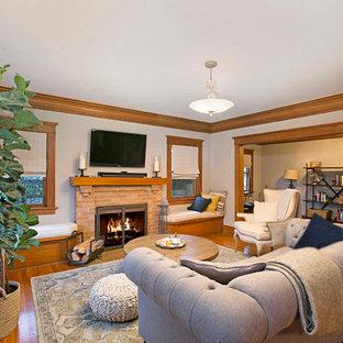 Cette image montre une salle de séjour craftsman de taille moyenne et fermée avec un mur gris, un sol en bois clair, une cheminée standard, un manteau de cheminée en brique, un téléviseur fixé au mur et un sol marron.