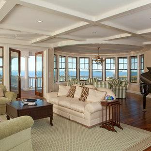 Exemple d'une grande salle de séjour bord de mer ouverte avec une salle de musique, un mur beige, aucune cheminée, un sol marron et un sol en bois foncé.