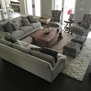 Modelo de sala de estar abierta, clásica renovada, de tamaño medio, con paredes grises, suelo de madera oscura, chimenea tradicional, marco de chimenea de piedra y suelo marrón
