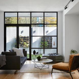 メルボルンのコンテンポラリースタイルのおしゃれなファミリールーム (白い壁、壁掛け型テレビ、暖炉なし、淡色無垢フローリング) の写真