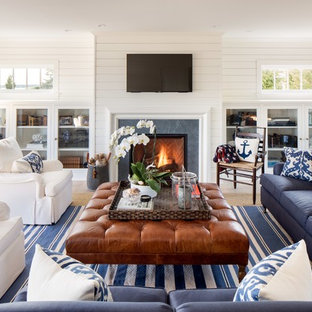 Inspiration for a large beach style open plan family and games room in New York with white walls, a standard fireplace, a wall mounted tv, light hardwood flooring and a tiled fireplace surround.