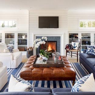 ニューヨークの大きいビーチスタイルのおしゃれなファミリールーム (白い壁、標準型暖炉、壁掛け型テレビ、淡色無垢フローリング、タイルの暖炉まわり) の写真
