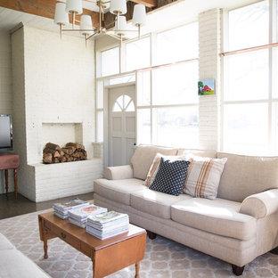 Ejemplo de sala de estar cerrada, de estilo de casa de campo, grande, con paredes blancas, estufa de leña, marco de chimenea de ladrillo, televisor independiente y suelo gris