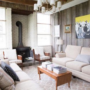 ニューオリンズの大きいカントリー風おしゃれな独立型ファミリールーム (白い壁、薪ストーブ、レンガの暖炉まわり、据え置き型テレビ、グレーの床) の写真